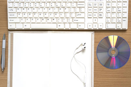 dvd rom: top view of keyboard computer notebook earphone and dvd disk on wood background