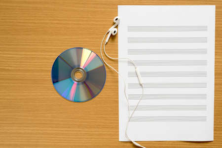 music staff: top view of music staff paper dvd dish and earphone on wood background