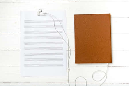 music staff: top view of earphone music staff paper and book on white wood background