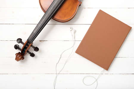 violin with notebook and earphone