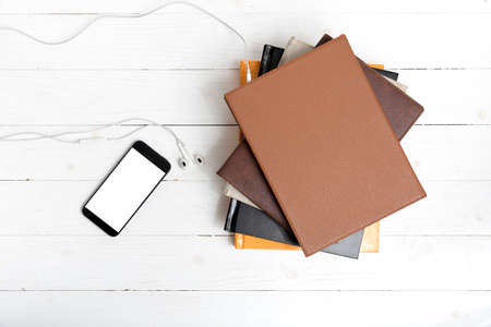 audible: top view of stack of book with phone and earphone on white wood background Stock Photo