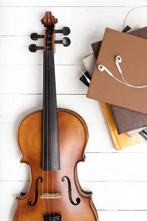 audio book: top view of violin with stack of book and earphone on white wood background