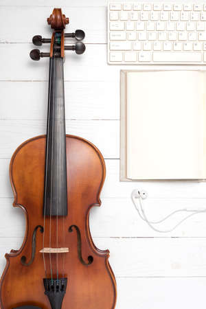 cellos: keyboard computer with notebook and violin on white wood background Stock Photo