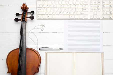 violin with keyboard computer music paper note and notebook on white wood background