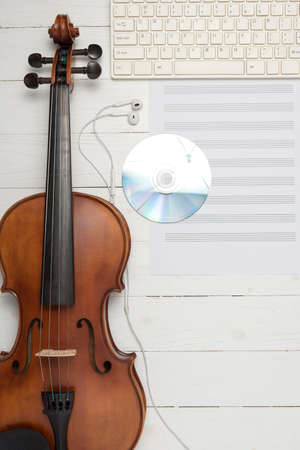 violin with keyboard computer music paper note and dvd disc on white wood background Stock Photo