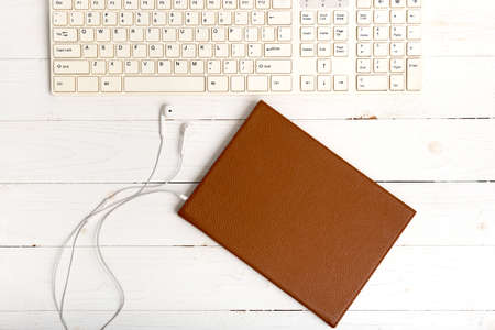 top view of keybard computer with notebook and earphone on white wood background Stock Photo