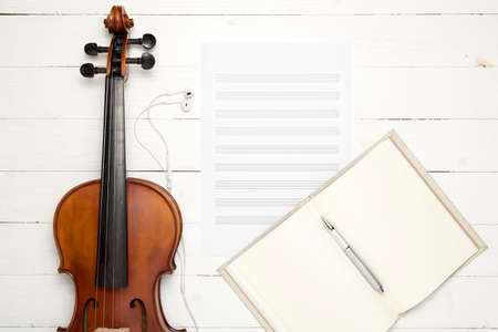 violin with music paper note and notebook on white wood background