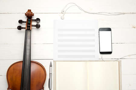 violin with keyboard computer music paper note and smart phone on white wood background