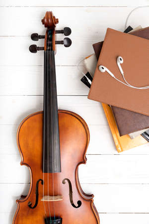 top view of violin with stack of book and earphone on white wood background