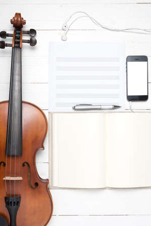 keyboard computer with notebook smart phone and violin on white background