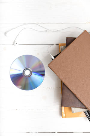 top view of earphone with stack of book and dvd disc on white wood background
