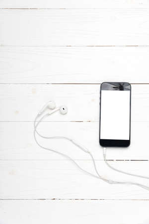 smart phone with earphone on white wood background Stock Photo