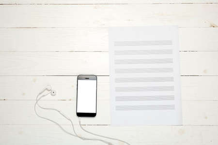 smart phone with music paper note on white wood background Stock Photo