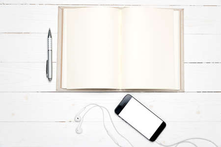 smart phone with open notebook on white wood background Stock Photo