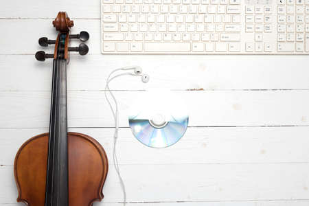 keyboard computer with dvd disc and violin on white wood background