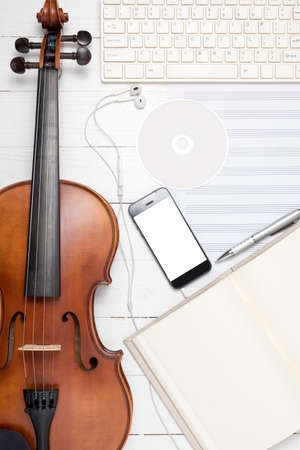 violin with keyboard computer music paper note dvd disc and smart phone on white wood background