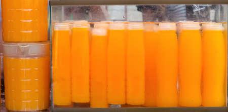 selling orange juice at Jatujak weekend market Bangkok Thailand. Imagens