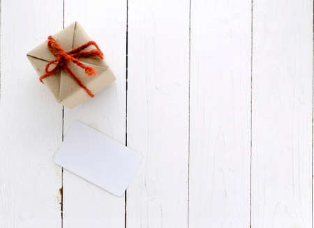 top view of craft gift box with card on white wood background