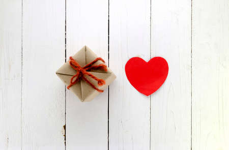 top view of craft gift box and heart concept vanlentine on white wood background