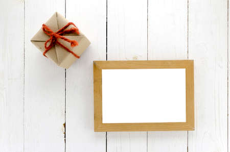top view of craft gift box with photo frame on white wood background
