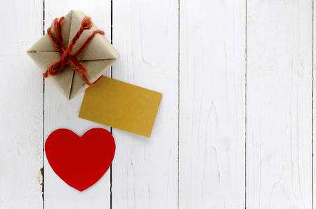 top view of craft gift with card heart on white wood background concept valentine