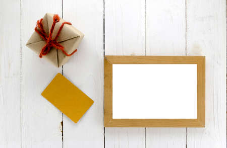 top view of gift box with card and photo frame on white wood background