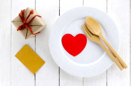 top view of craft box on dish and spoon fork on white wood background concept heart love
