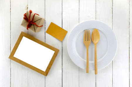 top view of craft box and dish and spoon fork on white wood background Imagens