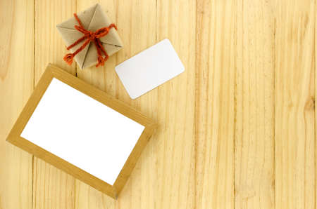 top view of craft gift box with photo frame on wood background