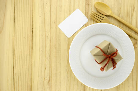 top view of craft gift box on dish on wood background concept food for gift