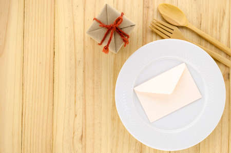 top view of craft gift box with envelope on wood background dish on wood background concept food for gift