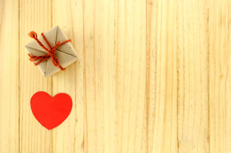 top view of craft gift box with heart on wood background concept love