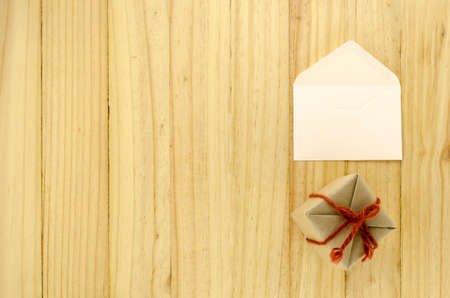 top view of craft gift box with envelope on wood background