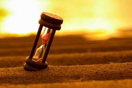 sand timer: Closeup of hourglass on the sand Timer Beach Sunrise