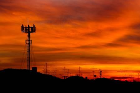 Telecommunicatie toren met zonsondergang hemel, silhouet Stockfoto