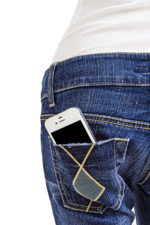 Mobile phone in the back pocket of blue jeans on white background photo