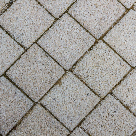 Paving slabs in the form of squares. Small gravel surface. photo