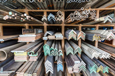 aluminum rod: series of different sizes metal pipes on shelf Stock Photo