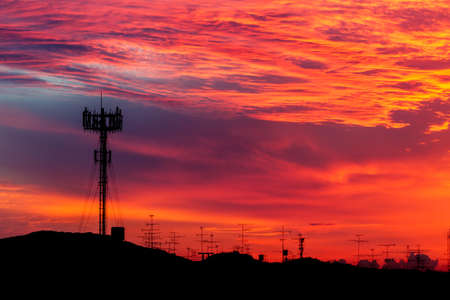 Telecommunications tower with sunset sky, silhouette  photo