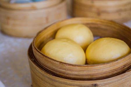 Steamed Egg Custard Bun (Lau Sah Bao, dim sum) in Bamboo Basket. photo