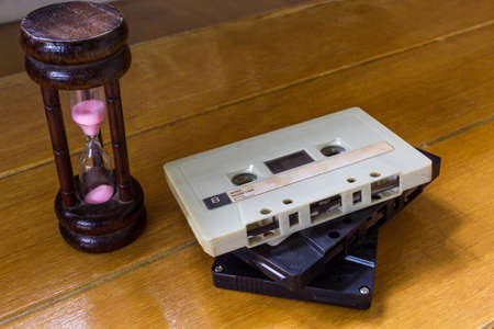 Hourglass and cassette tape on the wooden table. photo