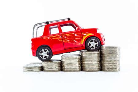 Auto rossa sopra un sacco di monete impilati isolato su sfondo bianco. Archivio Fotografico - 24374178