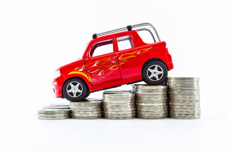 Red car over a lot of stacked coins isolated on white background.