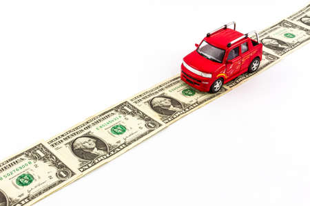 Red toy car on money road isolated on white background.  photo