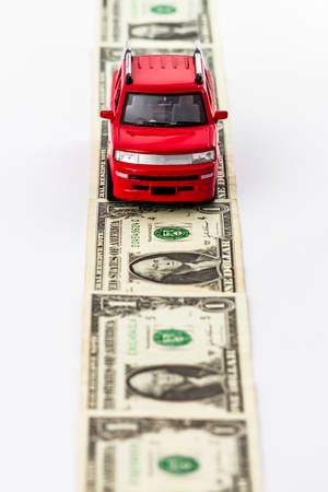 Red toy car on money road isolated on white . photo