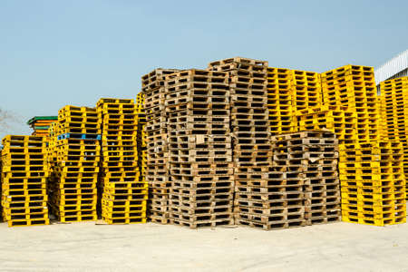 stacked up: Stacked up wooden pallets at cargo with blue sky. Stock Photo