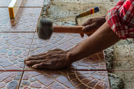 Construction mason worker floor tile installation. Home improvement.