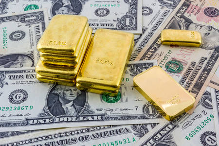 scrap gold: Gold bar on a heap of american dollars.  Stock Photo