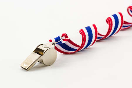 Metal Whistle and ribbon striped flag of thailand on a white background.   photo