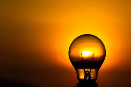 Close up light bulb with sunset sky background  photo